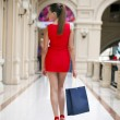 Beautiful smiling girl in a red dress, holding shopping bags — Stock Photo #70736735