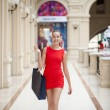 Beautiful smiling girl in a red dress, holding shopping bags — Stock Photo #70736755