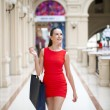 Beautiful smiling girl in a red dress, holding shopping bags — Stock Photo #70736777