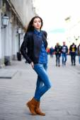 Young beautiful girl in blue jeans and a blue shirt on the backg — Stock Photo
