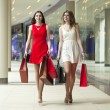 Two girlfriends on shopping walk on shopping mall with bags — Stock Photo #71355573