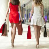 Two girlfriends on shopping walk on shopping mall with bags — Stock Photo