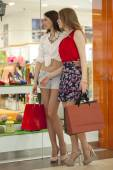 Two girlfriends on shopping walk on shopping centre with bags — Stock Photo