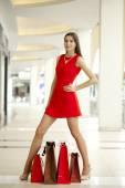 Dükkanda kırmızı seksi elbiseli güzel kadın — Stok fotoğraf