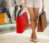 Legs of shopaholic wearing jeans shorts while carrying several p — Stock Photo