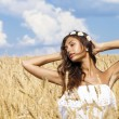 Young woman in a wheat golden field — Stock Photo #71897651