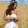 Young woman in a wheat golden field — Stock Photo #71897653