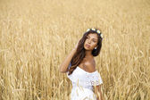 Close up portrait of a beautiful young brunette in a wheat field — Stock Photo