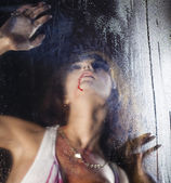 Terrible and bloody woman looking through wet glass — Stock Photo