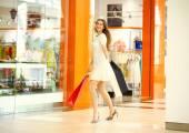Beautiful young woman holding shopping bags walking in the shop — Foto de Stock