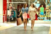 Two young women walking with shopping at the store — Photo