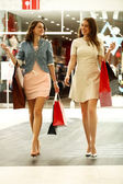 Two young women walking with shopping at the store — Stock Photo