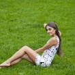 Sexy woman in short dress sitting on green grass — Stock Photo #72546087