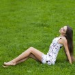 Sexy woman in short dress sitting on green grass — Stock Photo #72546095