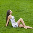 Sexy woman in short dress sitting on green grass — Stock Photo #72546101