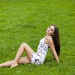 Sexy woman in short dress sitting on green grass — Stock Photo #72546109