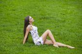 Sexy woman in short dress sitting on green grass — ストック写真