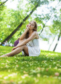 Young blonde woman on green meadow — Stock Photo