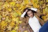 Young beautiful girl in blue jeans lying on yellow leaves — Stock Photo