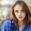 Close up of young beautiful woman in a checkered blue shirt — Stock Photo #75970479