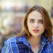 Close up of young beautiful woman in a checkered blue shirt — Stock Photo #75970619