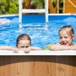 Two sisters in bikini near swimming pool. Hot Summer — Stock Photo #76073573