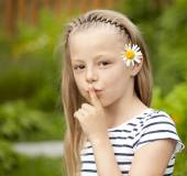 Little girl has put forefinger to lips as sign of silence — Stock Photo