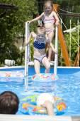 Two sisters in bikini near swimming pool. Hot Summer — Stock Photo