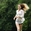 Young beautiful girl in the white shirt is running on the green — Stock Photo #76557395