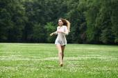 Young beautiful girl in the white shirt is running on the green  — Stock Photo