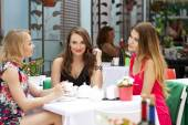 Three happy girlfriends woman sitting at a table in the summer c — Stock Photo