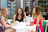 Three happy girlfriends woman sitting at a table in the summer c — Foto de Stock