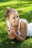 Happy beautiful blonde girl calling by phone in a summer park — Stock Photo