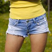 Beautiful woman body in denim jeans on summer street — Stock Photo