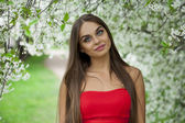 Portrait of a beautiful young girl in red dress on the backgroun — Stock Photo