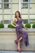 Beautiful young woman in long colorful dress — Stock Photo