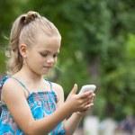 Portrait of brunette Caucasian schoolgirl with mobile phone — Stock Photo #77288576