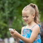 Portrait of brunette Caucasian schoolgirl with mobile phone — Stock Photo #77288594