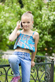 Little girl talking on cell phone against green of Park in summe — Stock Photo