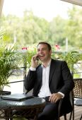 Young businessman using mobile phone at outdoor restaurant — Stock Photo