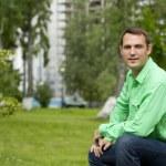 Stilig ung i en grön skjorta på bakgrund av sommaren — Stockfoto #77544042