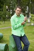 Young handsome man in a green shirt on the background of summer — Stock Photo
