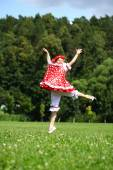 Little girl in a red sundress jumping for joy on the lawn — Stock Photo