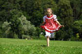 Little girl in a red polka-dot sundress into a major run on the — Stock Photo
