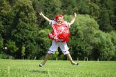 Menina em um vestido vermelho, pulando de alegria no gramado — Fotografia Stock