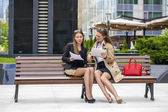 Two young beautiful business women sitting on a bench — Stock Photo
