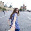 Young happy girl pulls the guys hand on the Red Square in Moscow — Stock Photo #78733576