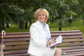 Portrait of serene mature woman in the summer park — Stock Photo