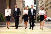 Team of five business people confidently striding along the summ — Stock Photo