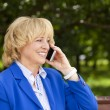 Portrait of an elderly beautiful woman talking on a cell phone — Stock Photo #79148400
